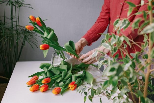 Preciosas tulipas vermelhas na mão de uma mulher uma florista europeia prepara um buquê de tulipas para um