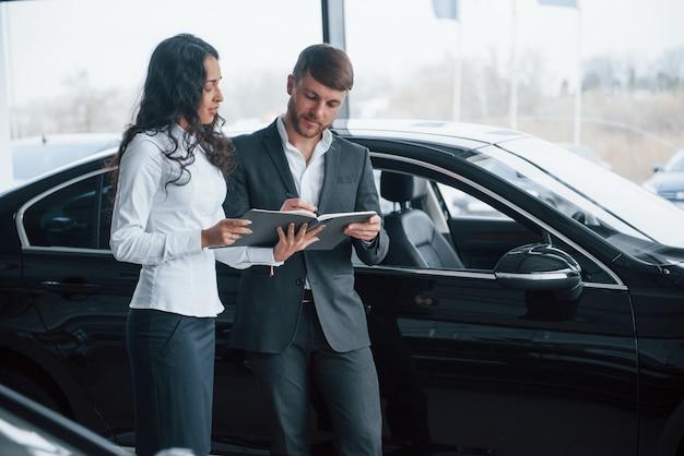 Precisa assinar esse documento. cliente do sexo feminino e empresário barbudo elegante e moderno no salão automóvel
