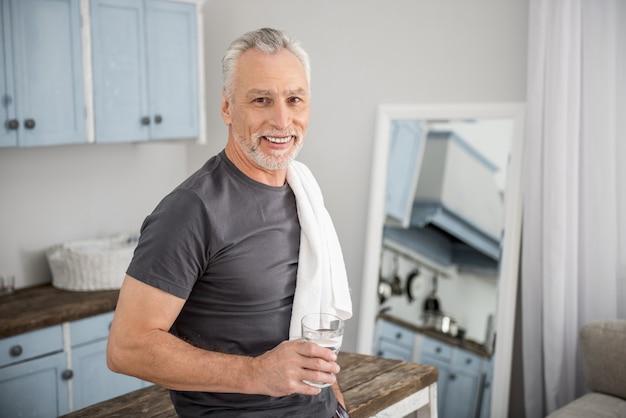 Precisa atualizar. homem maduro e alegre mantendo um sorriso no rosto e segurando um copo com água enquanto tem uma toalha no ombro
