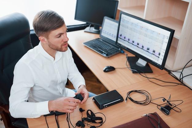 Precisa de algumas coisas antes de começarmos. o examinador de polígrafo trabalha no escritório com seu equipamento detector de mentiras