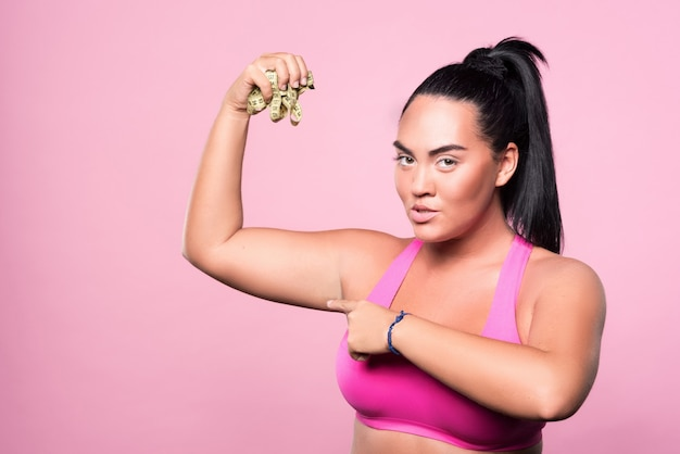 Precisa de menos centímetros. retrato de mulher mulata bem gordinha em pé e segurando a fita métrica de corpo amassado e apontando para o bíceps.
