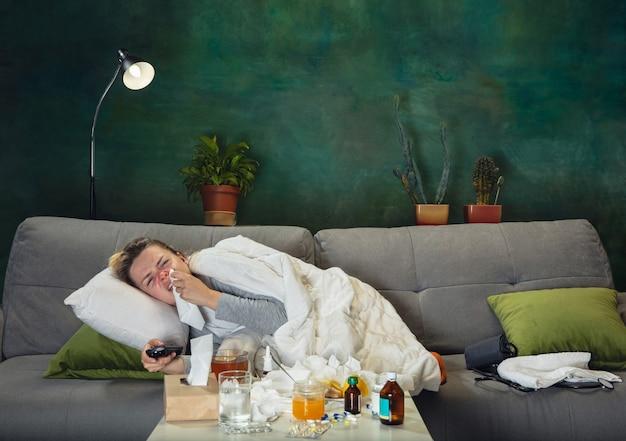 Precisa dormir. jovem doente, com febre e frio, sentindo-se doente, azul, fungando. parece sofredor e fraco, cobrindo com agasalho. resfriado, vírus, gripe sazonal. mulher sentada no sofá em casa.