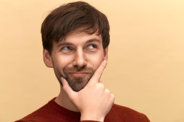Precisa escolher. foto de jovem com barba, vestindo um suéter, segura o queixo, franze os lábios com expressões sem noção, dúvidas sobre algo, posando contra uma parede bege