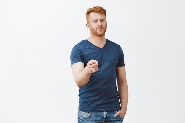 Precisamos de você, junte-se a nós. homem ruivo barbudo maduro, sério, bonito e confiante em uma camiseta azul casual, apontando com o dedo indicador olhando sério e estrito sobre a parede cinza