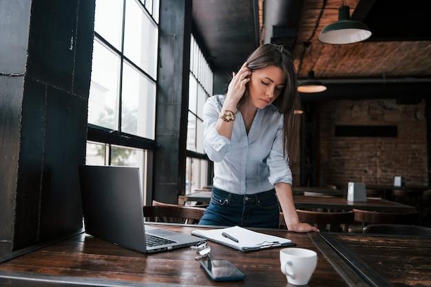 Preciso ter certeza se tudo está perfeito em meu relatório. mulher de negócios com roupas oficiais está dentro de casa no café durante o dia.