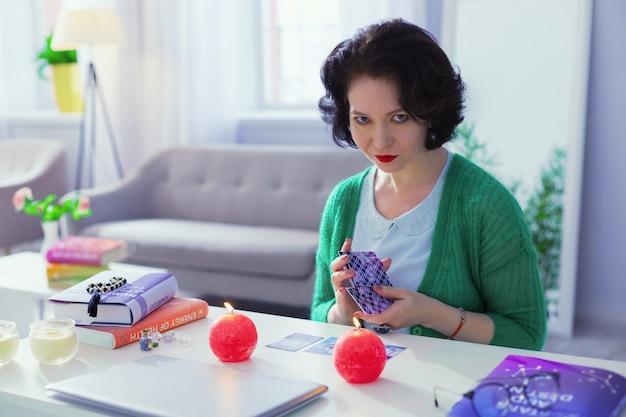 Predição do destino. cartomante inteligente profissional segurando cartas de tarô enquanto tem uma sessão online com um cliente