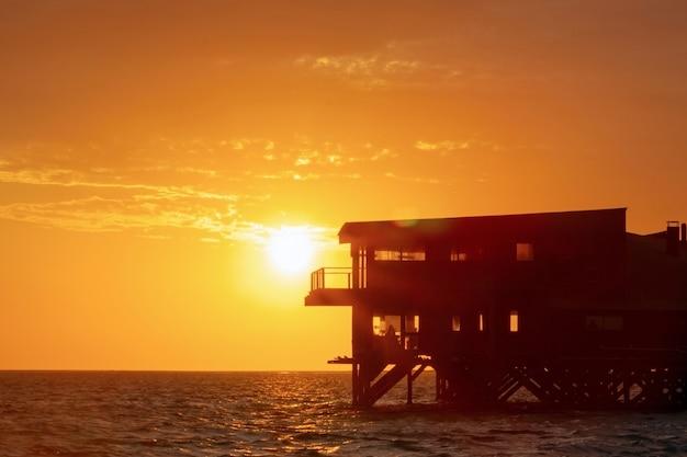 Prédio abandonado na água da lagoa, tendo como pano de fundo um pôr do sol dourado e brilhante