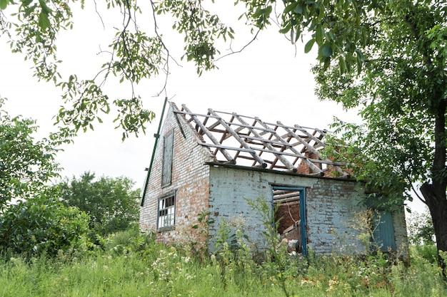 Prédio abandonado sem telhado em um campo coberto de vegetação