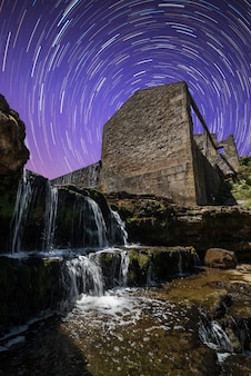 Prédio antigo em ruínas ao lado de uma cachoeira com o céu noturno