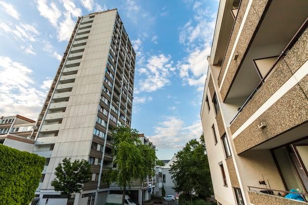 Prédio de apartamentos multistoried alto com as árvores contra o céu azul.