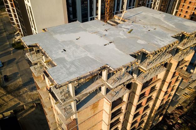 Prédio de apartamentos residencial de vários andares em construção. enquadramento em betão e tijolo de edifícios altos. incorporação imobiliária em área urbana.