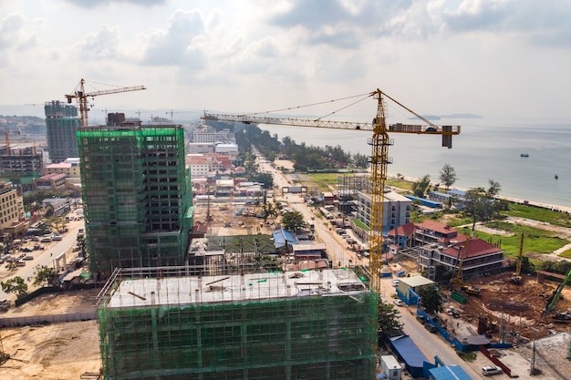Prédio de construção por guindaste na cidade perto do mar. construção de hotéis caros na cidade turística de sihanoukville, no camboja. muitos guindastes de construção. construção em escala.