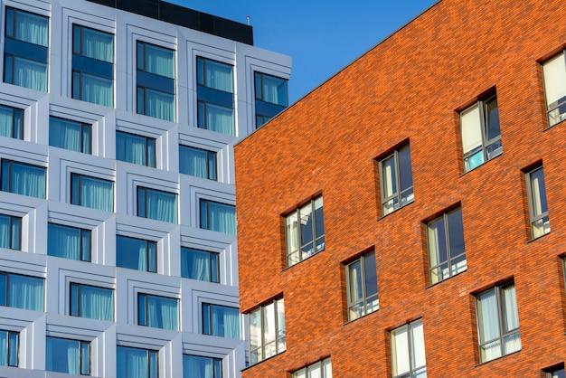 Prédio de escritórios do multi-andar feito do vidro e o prédio de escritórios do metal e do tijolo.