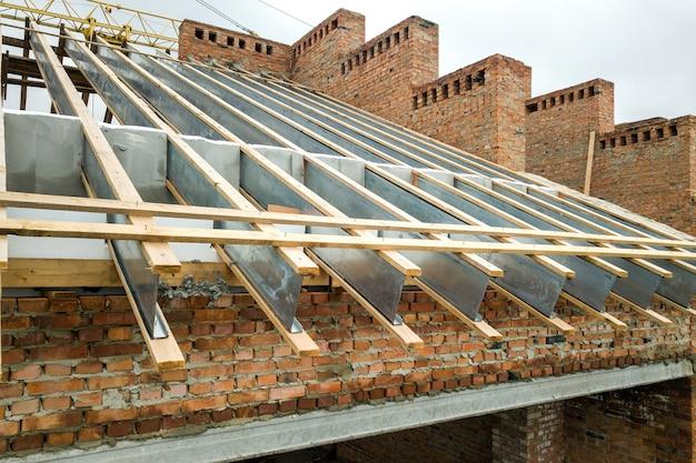 Prédio de tijolos inacabado com estrutura de telhado de madeira em construção.