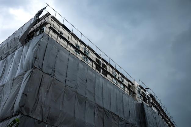 Prédio em construção com andaimes e rede de proteção para prevenção de poeira e acidentes