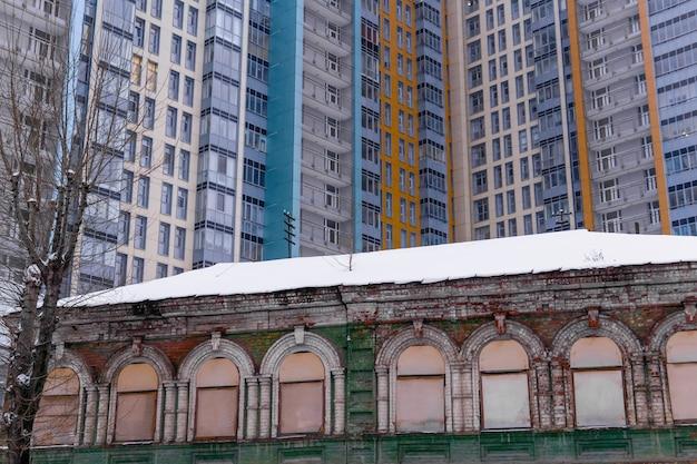 Prédio histórico abandonado com janelas fechadas com tábuas no fundo de um prédio moderno