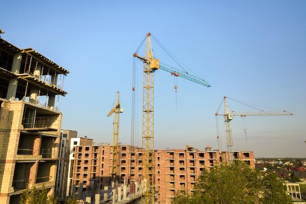 Prédios de apartamentos residenciais de vários andares em construção. enquadramento em betão e tijolo de habitações altas. incorporação imobiliária em área urbana.