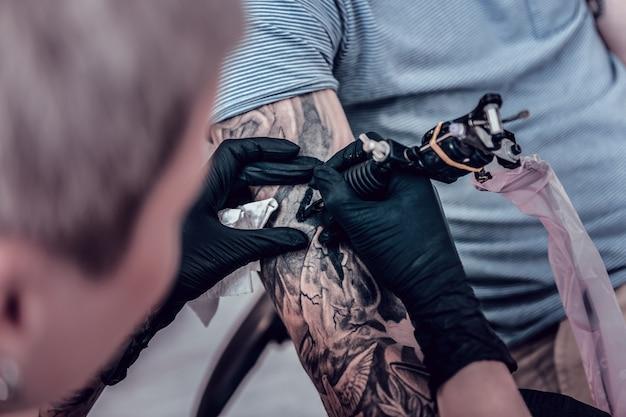 Preenchendo contornos pretos. artista preciso e preciso fazendo sombreamento para uma tatuagem massiva que ocupa a mão inteira