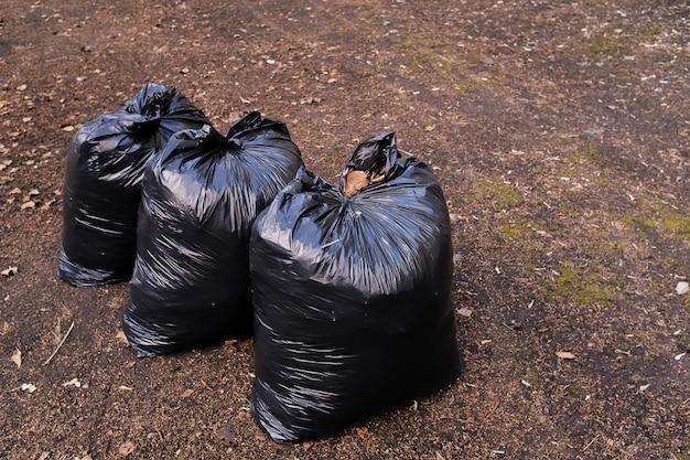 Preenchido com sacos de plástico preto lixo na natureza, em um parque público, ao longo da estrada.