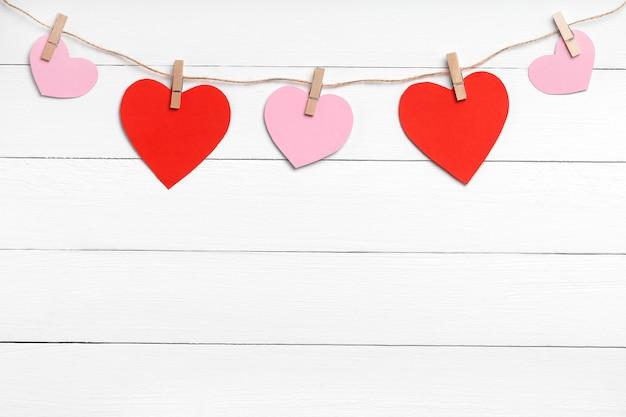 Pregadores de roupa com corações coloridos pendurados na corda atrás da superfície de madeira branca. copie o espaço, vista superior.