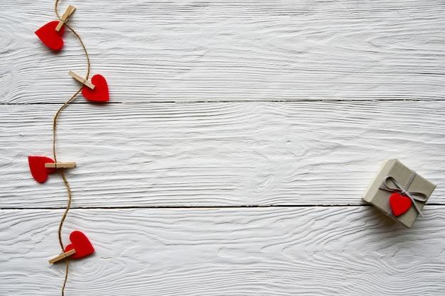 Pregadores de roupa com corações de feltro e caixa de presente em uma mesa branca. dia de são valentim