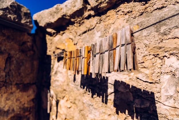 Pregadores de roupa de madeira para a roupa de suspensão com fundo rural de pedra envelhecido.