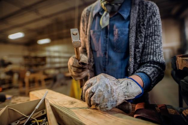 Pregar pregos de mulher na oficina de carpintaria