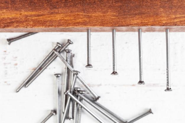 Pregos de ferro em uma mesa de madeira