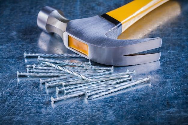 Pregos longos de construção inoxidável com martelo de garra no conceito de manutenção de fundo metálico riscado.