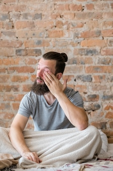 Preguiça matinal e exaustão. má noite de sono. homem sonolento sentado na cama e esfregando os olhos. copie o espaço.