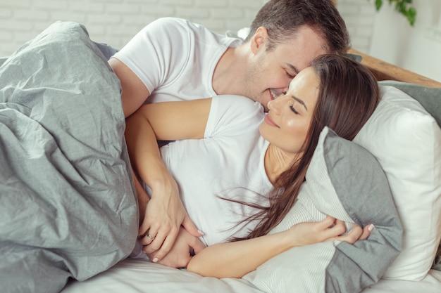 Preliminares de belo casal romântico na cama