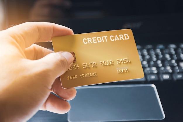 Prêmio do cartão de crédito na mão com fundo do teclado do computador