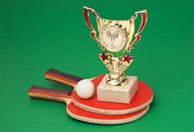 Prêmios esportivos e raquetes de tênis em uma mesa verde