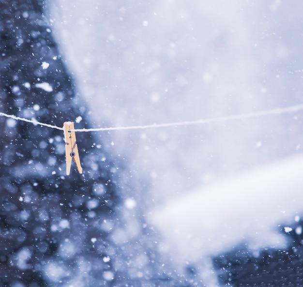 Prendedor de roupa colorido na corda em uma tempestade de neve ao ar livre