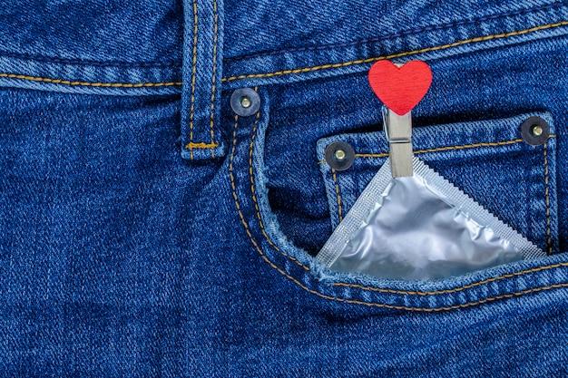 Prendedor de roupa com coração vermelho e camisinha no bolso da calça jeans. plano de fundo para o dia dos namorados.