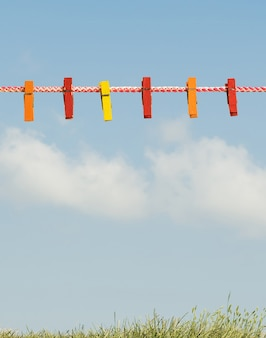 Prendedores de roupa coloridos em um varal contra o céu e a grama