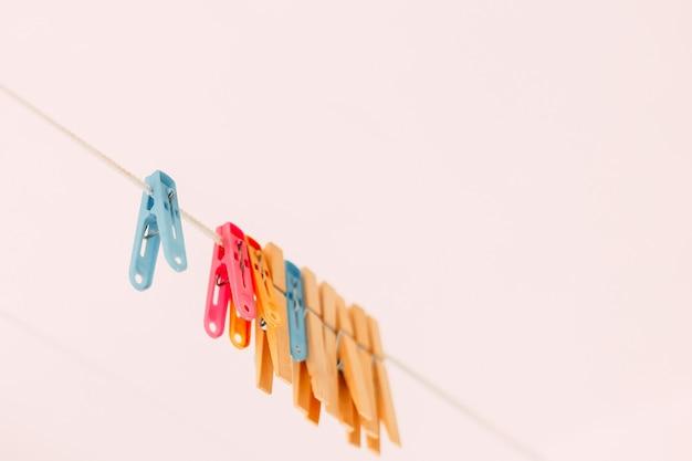 Prendedores de roupa coloridos em uma corda em um fundo desfocado