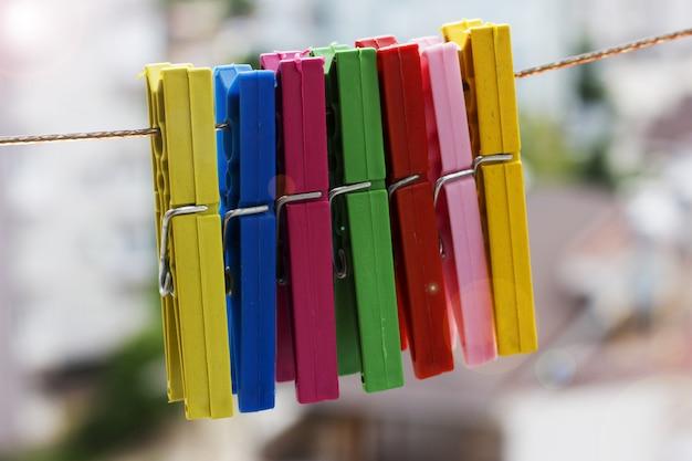 Prendedores de roupa coloridos pendurado em uma corda em um fundo da cidade