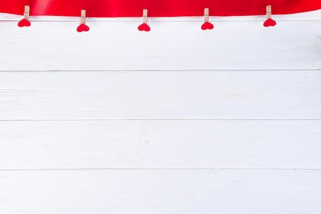 Prendedores de roupa com corações vermelhos em uma fita vermelha em um fundo branco de madeira do dia dos namorados