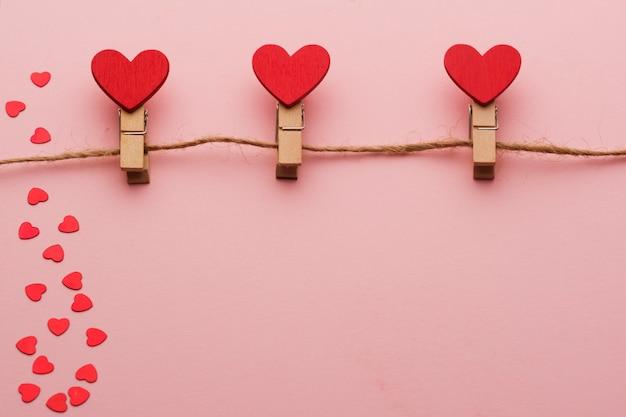 Prendedores de roupa de madeira com corações em uma corda em um fundo vermelho