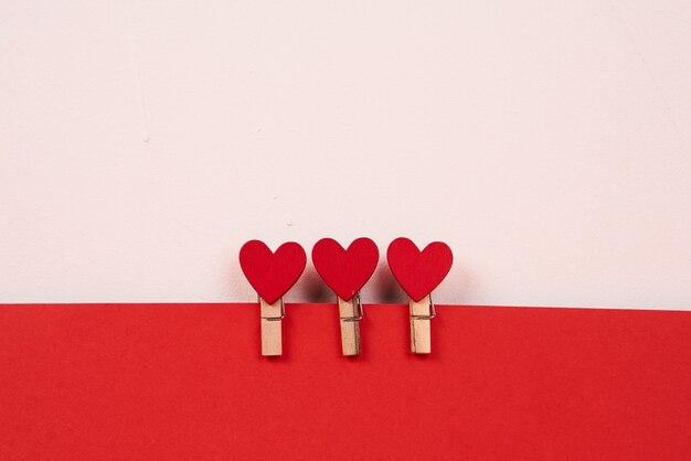 Prendedores de roupa de madeira com corações vermelhos em uma folha de papel