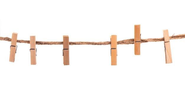 Prendedores de roupa de madeira com corda em uma superfície branca