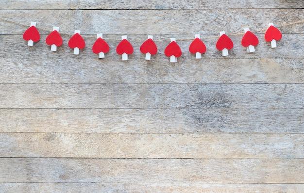 Prendedores de roupa feitos de madeira com formato de coração vermelho pendurados por uma corda marrom na mesa