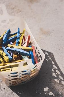 Prendedores de roupa plásticos pendurados em uma cesta. vista do topo.