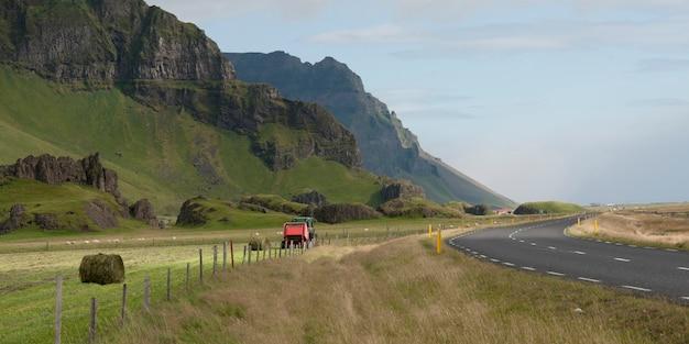 Prensa de feno fazendo fardos em terras agrícolas entre a encosta da montanha e rodovia