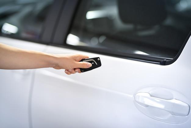 Prensas manuais femininas no controle remoto desbloqueiam os sistemas de alarme da porta do carro