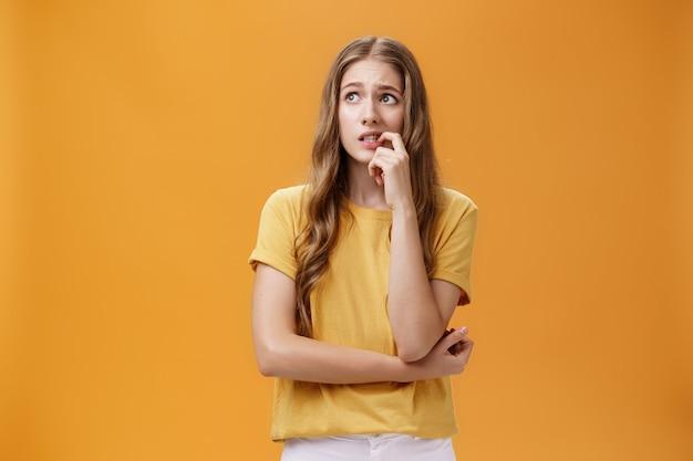 Preocupada, boba e insegura jovem aluna charmosa com longos cabelos ondulados louros nervosa mordendo f ...