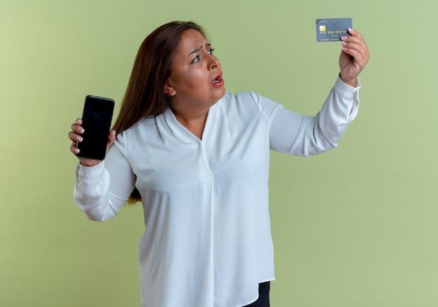 Preocupada casual caucasiana mulher de meia-idade segurando o telefone e olhando para o cartão de crédito na mão