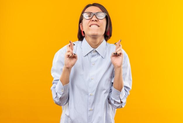 Preocupada com os olhos fechados, jovem e linda garota usando óculos, cruzando os dedos isolados na parede laranja