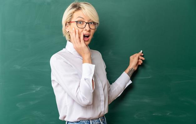 Preocupada jovem loira professora usando óculos na sala de aula em pé em vista de perfil na frente do quadro-negro apontando para o quadro-negro com giz olhando para frente mantendo as mãos no rosto